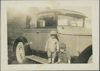 Two unidentified children in front of a car.
