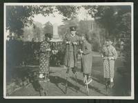 Children wearing school caps standing on stilts