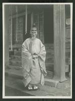 Shinto priest standing outside of a shrine