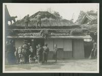 Group standing below workers putting a roof on a residential building