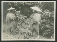 Two men dressed for rain gesturing at one another