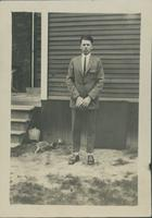 Harry Byers standing in front of the entrance to a house.