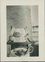 Glen[n] Mac McCourt sitting in a high chair.
