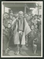 Japanese street crowd smiling from behind an aged man holding a stick