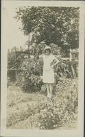 [Violet Byers] standing in garden.