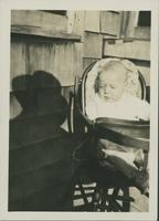 Unidentified baby in high chair.