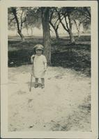 Child standing outside with gun.