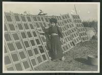 Woman standing next to seaweed drying racks