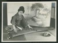 Seated woman playing a koto