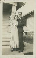 Unidentified couple standing in front of a house.