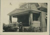 Marge Byers standing in front of house.