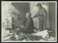 Man making umbrella as a child watches