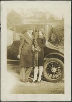 Couple standing in front of car.