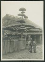Woman and two children standing outside of a home