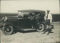 Harry Byers standing beside an automobile with 2 unidentified men inside it.