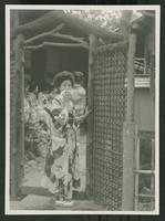 Woman standing at the door of a [restaurant?]