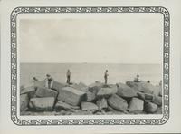 Unidentified people standing on rocks on shore.