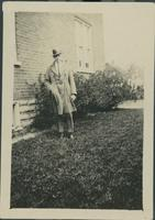 Harry Byers standing in the side yard of a house.