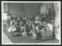 Seated adult holding infant seated next to collection of toy soldiers