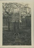 Harry Byers standing by a blossoming tree in a backyard.