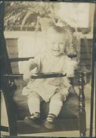 Infant sitting in chair.