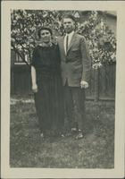 Harry Byers and an unidentified woman standing in a backyard.